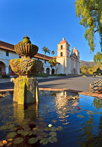 Exterior of the Santa Barbara Mission including a small pond and palm trees
