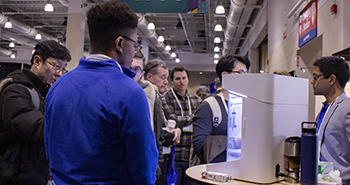 Exhibit attendees view a machine on display